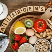 Allergy food concept. Allergy food as almonds, milk, pistachios, tomato, lemon, kiwi, trout, strawberry, bread, sesame seeds, eggs, peanuts and bean on wooden table