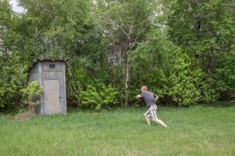 horizontal image of a man running to the out door toilet nestled in the green bushes on a summer day.