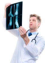 cheerful male doctor examining feet x-ray