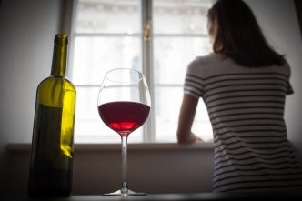Woman drinking wine alone in the dark room